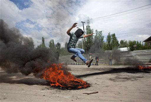 A Kashmiri Muslim protester jumps over a burning tire set up as a road block during a protest in Srinagar, India, Tuesday, Sept. 18, 2012, as part of widespread anger across the Muslim world about a film ridiculing Islam&#39;s Prophet Muhammad. &#40;AP Photo&#47; Dar Yasin&#41; <span class=meta>(AP Photo&#47; Dar Yasin)</span>