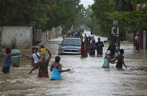 Residents wade through a flooded street triggered by Tropical Storm Isaac in Port-au-Prince, Haiti, Saturday, Aug. 25, 2012. Tropical Storm Isaac swept across Haiti&#39;s southern peninsula early Saturday, dousing a capital city prone to flooding and adding to the misery of a poor nation still trying to recover from the 2010 earthquake. &#40;AP Photo&#47;Dieu Nalio Chery&#41; <span class=meta>(AP Photo&#47; Dieu Nalio Chery)</span>
