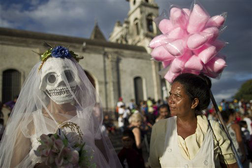 "<div class=""meta image-caption""><div class=""origin-logo origin-image ""><span></span></div><span class=""caption-text"">A street vendor, right, looks at a disguised reveler during celebrations marking the 9th International Poetry Festival honoring Nicaraguan poet, priest and former Nicaragua's Culture Minister, Ernesto Cardenal, not in picture, in Granada, Nicaragua, Wednesday, Feb 20, 2013. The festival is attended by more than 300 poets from some 60 countries. (AP Photo/Esteban Felix)</span></div>"