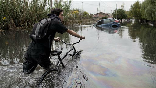 A man pushes his bike through a flooded street in La Plata, in Argentina&#39;s Buenos Aires province, Wednesday, April 3, 2013. At least 35 people were killed by flooding overnight in Argentina&#39;s Buenos Aires province, the governor said Wednesday, bringing the overall death toll from days of torrential rains to at least 41 and leaving large stretches of the provincial capital under water. &#40;AP Photo&#47;Natacha Pisarenko&#41; <span class=meta>(AP Photo&#47; Natacha Pisarenko)</span>