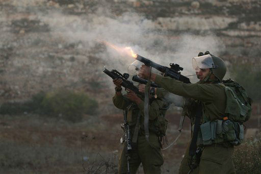 "<div class=""meta ""><span class=""caption-text "">An Israeli border policeman fires a tear gas canister during a protest against Israel's operations in Gaza Strip, outside Ofer, an Israeli military prison near the West Bank city of Ramallah, Sunday, Nov. 18, 2012.(AP Photo/Majdi Mohammed) (AP Photo/ Majdi Mohammed)</span></div>"