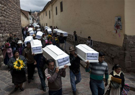 People carry coffins containing the remains of people whose bodies were excavated, to a church in Cuzco, Peru, Tuesday, Feb. 19, 2013. Authorities turned over to families 26 coffins containing the remains of people from various towns whose body parts were excavated from 250 graves since November. According to Peruvian authorities, the victims, including women, children and village authorities, were killed by both members of the Shining Path militant group and the army between 1980 and 2000, and are among tens of thousands of Peruvians who died during the Maoist-inspired insurgency. (AP Photo/Martin Mejia)
