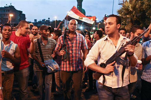 "<div class=""meta ""><span class=""caption-text "">Plainclothes policemen walk with protesters opposed to Egyptian President Mohammed Morsi at the site of clashes with opposing protesters in the Kit Kat neighborhood of Giza, Egypt, Tuesday, July 2, 2013. With a military deadline for intervention ticking down, hundreds of thousands of protesters seeking the ouster of Egypt's Islamist president sought Tuesday to push the embattled leader further toward the edge with another massive show of resolve and unity. Witnesses said that armed and masked men marching with Muslim Brotherhood protesters fired pellets at protesters holding a sit in in the Kit Kat area, leaving a number of people injured. Police men in plain clothes held their automatic rifles and sided by protesters to disperse the Muslim Brotherhood protesters. (AP Photo/Roger Anis, El Shorouk Newspaper) EGYPT OUT (AP Photo/ Roger Anis)</span></div>"