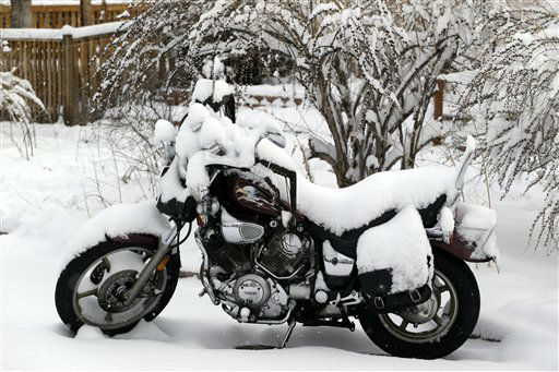 A motorcycle is covered in snow on a residential street in Denver on Thursday, Feb. 21, 2013. A fast moving winter storm passed through Colorado Wednesday night and Thursday morning dropping as much as a foot of snow in areas of the state. &#40;AP Photo&#47;Ed Andrieski&#41; <span class=meta>(AP Photo&#47; Ed Andrieski)</span>