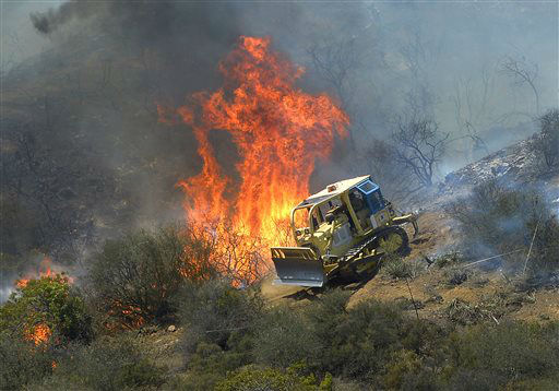 "<div class=""meta image-caption""><div class=""origin-logo origin-image ""><span></span></div><span class=""caption-text"">A bulldozer clears a firebreak near a wildfire burning along a hillside near homes in Thousand Oaks, Calif., Thursday, May 2, 2013. A Ventura County Fire Department spokeswoman said the blaze that broke out Thursday morning near Camarillo and Thousand Oaks, 50 miles west of Los Angeles, had spread to over 6,500 acres, forcing evacuations of nearby neighborhoods. (AP Photo/Mark J. Terrill) (AP Photo/ Mark J. Terrill)</span></div>"