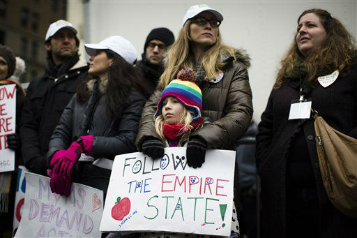 Arla Graham, 8, of Brooklyn, holds a sign that reads &#34;Follow the Empire State&#34; outside city hall park during the One Million Moms for Gun Control Rally, Jan. 21, 2012, in New York. New York State has recently passed some of the strictest gun laws in the nation following the school shooting in Newtown, Ct. Demonstrators called for new gun control legislation, demanding a ban on assault weapons and stricter regulations on gun purchases. &#40;AP Photo&#47;John Minchillo&#41; <span class=meta>(AP Photo&#47; John Minchillo)</span>