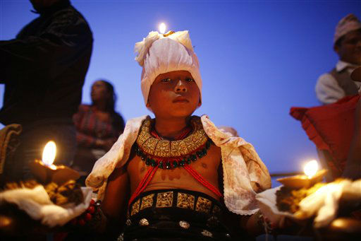 A young Nepalese Hindu devotee stands with burning oil lamps on his body as part of rituals to celebrate the tenth and final day of Dashain festival at Bhaktapur, also known as the city of devotees, on the outskirts of Katmandu, Nepal, Wednesday, Oct. 24, 2012. The festival commemorates the slaying of a demon king by Hindu goddess Durga, marking the victory of good over evil. &#40;AP Photo&#47;Niranjan Shrestha&#41; <span class=meta>(AP Photo&#47; Niranjan Shrestha)</span>