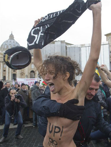 "<div class=""meta ""><span class=""caption-text "">Italian police officers stop members of a group of four women who went topless to protest the Vatican's opposition to gay marriage, in St. Peter's Square at the Vatican, Sunday, Jan. 13, 2013. Police quickly took the women away, and the pope appeared not to have been disturbed as he delivered his traditional prayer from his studio window overlooking the piazza. On their bare backs, the women had painted slogans ""In Gay We Trust,"" and ""Shut Up. (AP Photo/Angelo Carconi) (AP Photo/ Angelo Carconi)</span></div>"