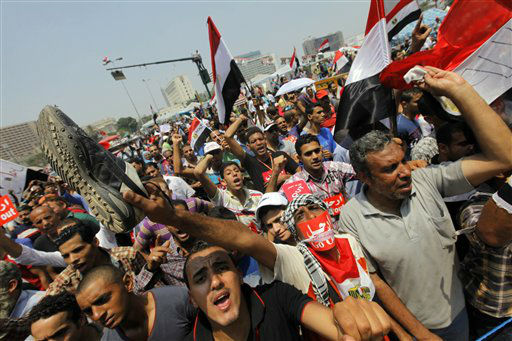 "<div class=""meta ""><span class=""caption-text "">Opponents of Egypt's Islamist President Mohammed Morsi shout slogans during a protest in Tahrir Square in Cairo, Egypt, Wednesday, July 3, 2013. A Defense Ministry official said army chief Gen. Abdel-Fattah el-Sissi is meeting with his top commanders, hours before the military's deadline to the president and opposition to resolve the nation's political crisis is set to expire. Arabic reads, ""Leave."" (AP Photo/Amr Nabil) (AP Photo/ Amr Nabil)</span></div>"