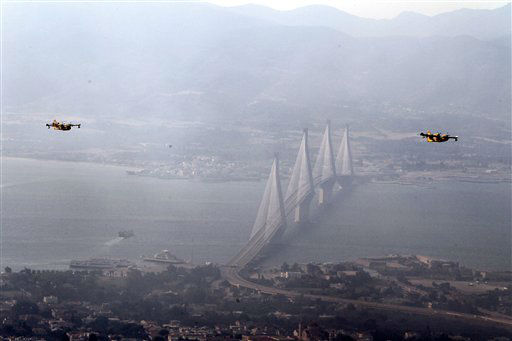 Aircrafts fly over the western Greek port city of Patras as the bridge of Rio-Antirion bridge is seen in the background during a wildfire on Wednesday, July 18, 2012. Greek authorities declared a state of emergency near the country&#39;s third-largest city Wednesday due to raging wildfires, but officials said no inhabited areas were under immediate threat. &#40;AP Photo&#47;Thanassis Stavrakis&#41; <span class=meta>(AP Photo&#47; Thanassis Stavrakis)</span>