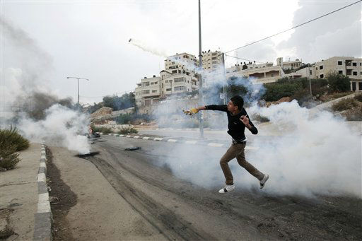 A Palestinian throws back a tear gas canister  during a protest against Israel&#39;s operations in Gaza Strip, outside Ofer, an Israeli military prison near the West Bank city of Ramallah, Sunday, Nov. 18, 2012. &#40;AP Photo&#47;Majdi Mohammed&#41; <span class=meta>(AP Photo&#47; Majdi Mohammed)</span>