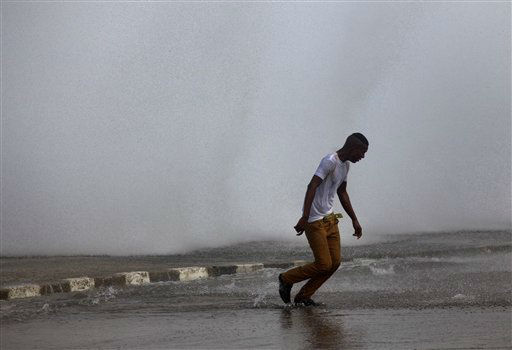A youth turns his back to a wave crashing against the Malecon after the passing of Hurricane Sandy in Havana, Cuba, Thursday, Oct. 25, 2012. Hurricane Sandy blasted across eastern Cuba on Thursday as a potent Category 2 storm and headed for the Bahamas after causing at least two deaths in the Caribbean. &#40;AP Photo&#47;Ramon Espinosa&#41; <span class=meta>(AP Photo&#47; Ramon Espinosa)</span>