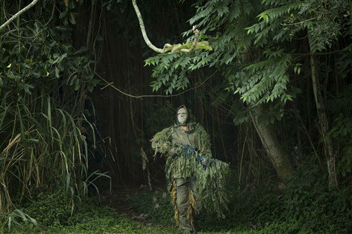 A Brazilian Navy sniper participates in a mock hostage rescue drill in Rio de Janeiro, Brazil, Monday, May 27, 2013. The Brazilian Navy conducted the drill in preparation for the Confederation Cup that runs from June 15-30. (AP Photo/Victor R. Caivano)