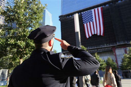 A New York City Police officer salutes a flag hanging from the One World Trade Center building, during ceremonies for the 11th anniversary of the attacks at the World Trade Center, in New York, Tuesday Sept. 11, 2012. &#40;AP Photo&#47;John Moore, Pool, Getty Images&#41; <span class=meta>(AP Photo&#47; John Moore)</span>
