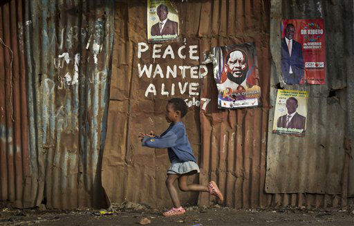 A young girl runs past pro-peace graffiti written during the post-election violence of the previous election in 2007 and a poster of presidential candidate Raila Odinga, center-right, in the Kibera slum of Nairobi, Kenya Wednesday, March 6, 2013. Election officials in Kenya transported their ballot counts to be tallied in the capital Wednesday after the preliminary electronic vote counting system broke down, while the coalition of a top presidential candidate levied charges of meddling against Britain&#39;s High Commissioner. &#40;AP Photo&#47;Ben Curtis&#41; <span class=meta>(AP Photo&#47; Ben Curtis)</span>