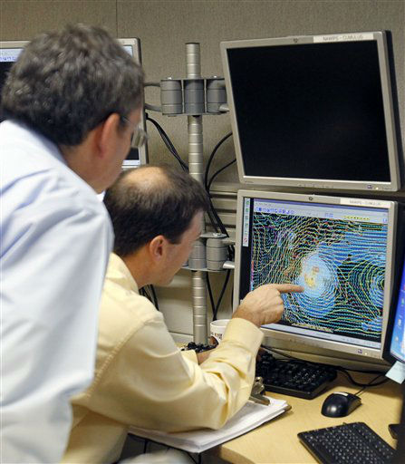 Senior hurricane specialist Dan Brown, right, points to a satellite image of Sandy to James Franklin, chief hurricane specialist, in preparation of the 11:00 EDT advisory at the National Hurricane Center in Miami, Saturday, Oct. 27, 2012. Early Saturday, the storm was about 335 miles southeast of Charleston, S.C. Tropical storm warnings were issued for parts of Florida&#39;s East Coast, along with parts of coastal North and South Carolina and the Bahamas. Tropical storm watches were issued for coastal Georgia and parts of South Carolina, along with parts of Florida and Bermuda. Sandy is projected to hit the Atlantic Coast early Tuesday. &#40;AP Photo&#47;Alan Diaz&#41; <span class=meta>(AP Photo&#47; Alan Diaz)</span>