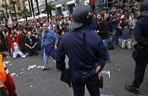 Protestors shout slogans as a riot policeman  hides his nightstick during the demonstration at the parliament against austerity measures announced by the Spanish government in Madrid, Spain, Tuesday, Sept. 25, 2012. Spain&#39;s Parliament has taken on the appearance of a heavily guarded fortress with dozens of police blocking access from every possible angle, hours ahead of a protest against the conservative government&#39;s handling of the economic crisis. The demonstration, organized behind the slogan &#39;Occupy Congress,&#39; is expected to draw thousands of people. It is due to start around 1730 GMT Tuesday. Madrid authorities said some 1,300 police would be deployed. The protestors call for Parliament to be dissolved and fresh elections held, claiming the government&#39;s austerity measures show the ruling Popular Party misled voters to get elected last November. &#40;AP Photo&#47;Andres Kudacki&#41; <span class=meta>(AP Photo&#47; Andres Kudacki)</span>