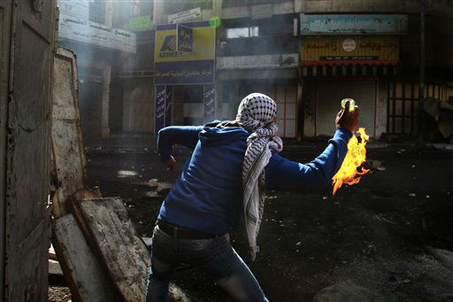 A Palestinian protester throws a Molotov cocktail towards Israeli soldiers, not pictured, during clashes in the West Bank city of Hebron, Wednesday, April 3, 2013. Palestinian prisoners have been rioting and hunger striking since a 64-year-old prisoner died of throat cancer on Tuesday. The Palestinians have blamed Israel for the man&#39;s death, saying he was not given proper medical care. The prisoner, Maysara Abu Hamdiyeh, had been serving a life sentence for his role in a foiled attempt to bomb a busy cafe in Jerusalem in 2002. &#40;AP Photo&#47;Nasser Shiyoukhi&#41; <span class=meta>(AP Photo&#47; Nasser Shiyoukhi)</span>