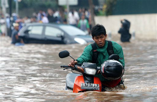 "<div class=""meta image-caption""><div class=""origin-logo origin-image ""><span></span></div><span class=""caption-text"">A man pushes his motorcycle through a flooded street in Jakarta, Indonesia, Thursday, Jan. 17, 2013. Floods regularly hit parts of Jakarta in the rainy season, but Thursday's inundation following an intense rain storm appeared especially widespread. (AP Photo/Tatan Syuflana.)</span></div>"