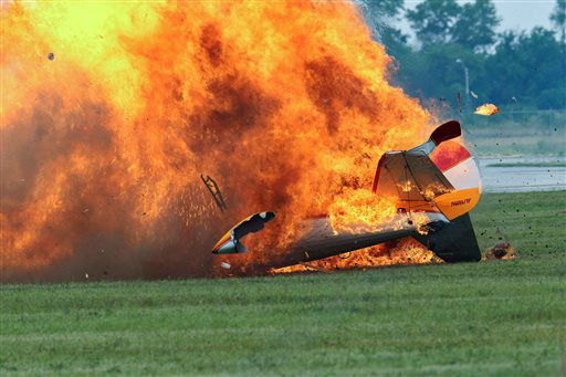 Flames erupt from a stunt plane after it crashed during a wing walker&#39;s performance at the Vectren Air Show, Saturday, June 22, 2013, in Dayton, Ohio. The crash killed the pilot and the wing walker instantly, authorities said. &#40;AP Photo&#47;Thanh V Tran&#41; MANDATORY CREDIT DOMESTIC USE ONLY. FOR INTERNATIONAL USE CONTACT AP IMAGES <span class=meta>(AP Photo&#47; Thanh V Tran)</span>