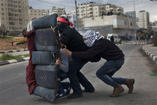 Masked Palestinians use a back car seat as a shield during a protest to support Palestinian prisoners, outside Ofer, an Israeli military prison near the West Bank city of Ramallah, Tuesday, Feb. 19, 2013. Palestinian protesters clashed with Israeli soldiers at a rally Tuesday in support of four imprisoned Palestinians on hunger strike, as hundreds of inmates said they were refusing food for the day in solidarity with the fasting inmates. One of the four hunger-striking Palestinians is 35-year-old Samer Issawi whose health has severely deteriorated after he has refused food, on-and-off, for more than 200 days. (AP Photo/Bernat Armangue)