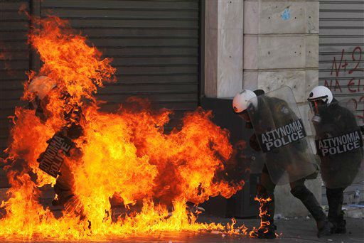 Riot policemen on fire after a petrol bomb thrown by protesters ignited during a nationwide general strike in Athens, Wednesday, Sept. 26, 2012. Police clashed with protesters hurling petrol bombs and bottles in central Athens Wednesday after an anti-government rally called as part of a general strike in Greece turned violent. &#40;AP Photo&#47;Petros Giannakouris&#41; <span class=meta>(AP Photo&#47; Petros Giannakouris)</span>