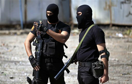 Two Egyptian police officers wear masks as they stand guard during clashes with protesters, not seen, near the state security building in Port Said, Egypt, Wednesday, March 6, 2013. Clashes between protesters and police have broken out in this restive Egyptian port city despite efforts by the military to separate the two sides. &#40;AP Photo&#47;Khalil Hamra&#41; <span class=meta>(AP Photo&#47; Khalil Hamra)</span>