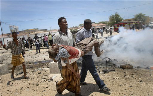 Somali men carry a seriously wounded man after a car bomb blast close to the Somali government&#39;s, headquarters in the capital Mogadishu, Somalia Monday, March 18, 2013. An explosives-laden car that apparently was targeting a truck full of Somali government officials instead hit a civilian car and exploded, setting a nearby mini-bus on fire and killing at least seven people Monday, police and witnesses said.  &#40;AP Photo&#47;Farah Abdi Warsameh&#41; <span class=meta>(AP Photo&#47; Farah Abdi Warsameh)</span>