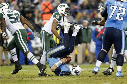 Tennessee Titans quarterback Jake Locker ends up on his back after being hit in the fourth quarter of an NFL football game against the New York Jets on Monday, Dec. 17, 2012, in Nashville, Tenn. Defending for the Jets are David Harris &#40;52&#41; and Antonio Allen &#40;39&#41;. &#40;AP Photo&#47;Joe Howell&#41; <span class=meta>(AP Photo&#47; Joe Howell)</span>