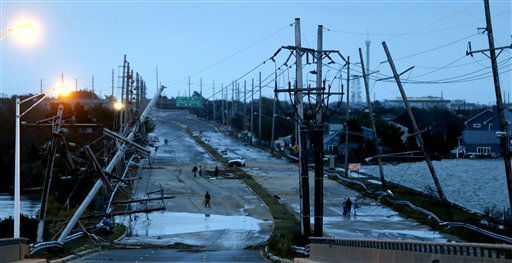 "<div class=""meta ""><span class=""caption-text "">Downed power lines and a battered road is what superstorm Sandy left behind as people walk off the flooded Seaside Heights island, Tuesday, Oct. 30, 2012. Sandy, the storm that made landfall Monday, caused multiple fatalities, halted mass transit and cut power to more than 6 million homes and businesses. (AP Photo/Julio Cortez) (AP Photo/ Julio Cortez)</span></div>"
