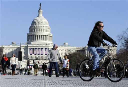 A man rides a bicycle as others walk on the National Mall Sunday, Jan. 20, 2013, with the U.S. Capitol prepared for the ceremonial swearing-in of President Barack Obama, the 57th Presidential Inaugural on Monday in Washington. &#40;AP Photo&#47;Alex Brandon&#41; <span class=meta>(AP Photo&#47; Alex Brandon)</span>