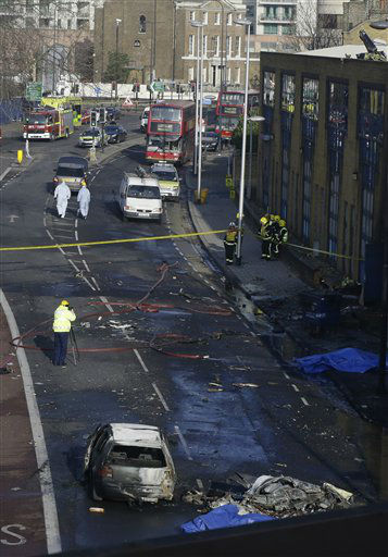 Remnants of a helicopter, bottom right, which crashed onto a construction crane are seen on the ground by a burnt out car in London, Wednesday, Jan. 16, 2013. The helicopter crashed into a crane and fell on a crowded street in central London during rush hour Wednesday, sending black plumes of smoke into the air as it smashed to the ground. The pilot and one person on the ground were killed and 13 others injured, officials said. &#40;AP Photo&#47;Lefteris Pitarakis&#41; <span class=meta>(AP Photo&#47; Lefteris Pitarakis)</span>