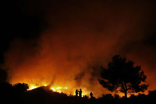 Villagers watch a wildfire burning between Chirokitia and Kato Dris villages in Larnaca district, south of the island of Cyprus, Sunday, Aug. 12, 2012.   Cypriot authorities have ordered the evacuation of a small, hillside village near the island southern coast as a large brushfire continues to rage out of control nearby. The blaze started Sunday afternoon and spread quickly because of strong wings, scorching many hectares of trees and wild brush. &#40;AP Photo&#47;Petros Karadjias&#41; <span class=meta>(AP Photo&#47; Petros Karadjias)</span>