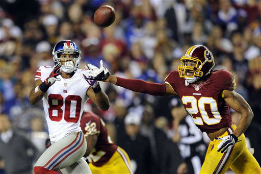 New York Giants wide receiver Victor Cruz &#40;80&#41; pulls in a pass under pressure from Washington Redskins defensive back Cedric Griffin &#40;20&#41; during the first half of an NFL football game in Landover, Md., Monday, Dec. 3, 2012. &#40;AP Photo&#47;Nick Wass&#41; <span class=meta>(AP Photo&#47; Nick Wass)</span>