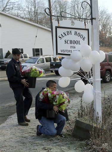 Volunteer firefighters place flowers at a makeshift memorial at a sign for the Sandy Hook Elementary school Saturday, Dec. 15, 2012 in the Sandy Hook village of Newtown, Conn. The massacre of 26 children and adults at Sandy Hook Elementary school elicited horror and soul-searching around the world even as it raised more basic questions about why the gunman, 20-year-old Adam Lanza, would have been driven to such a crime and how he chose his victims. &#40;AP Photo&#47;Mary Altaffer&#41; <span class=meta>(AP Photo&#47; Mary Altaffer)</span>