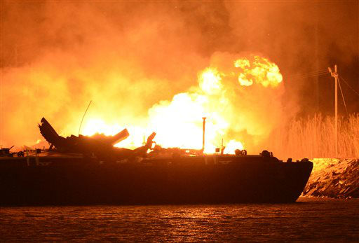A massive explosion at 3a.m. EDT on one of the two barges still ablaze in the Mobile River in Mobile, Ala., on Thursday, April 25, 2013. Three people were injured in the blast. Fire officials have pulled units back from fighting the fire due to the explosions and no immediate threat to lives. &#40;AP Photo John David Mercer&#41; Three people were hospitalized with burns. Information on their conditions was not immediately available. <span class=meta>(AP Photo&#47; John David Mercer)</span>