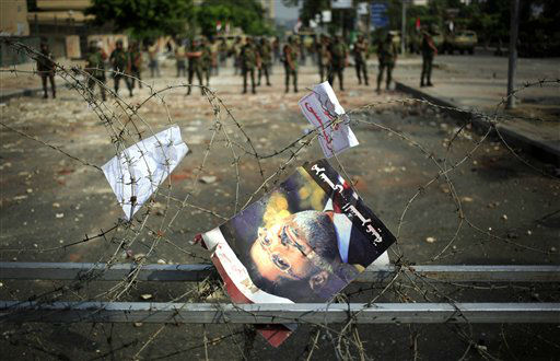 A poster of ousted President Mohammed Morsi hangs on the barbed wire at the Republican Guard building in Nasr City, Cairo, Egypt, Tuesday, July 9, 2013. Egyptian security forces killed dozens of supporters of Egypt&#39;s ousted president in one of the deadliest single episodes of violence in more than two and a half years of turmoil. The toppled leader&#39;s Muslim Brotherhood called for an uprising, accusing troops of gunning down protesters, while the military blamed armed Islamists for provoking its forces. &#40;AP Photo&#47;Khalil Hamra&#41; <span class=meta>(AP Photo&#47; Khalil Hamra)</span>