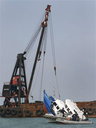 A partially submerged boat is stabilized by the crane of another vessel after it collided with a ferry Monday night near Lamma Island, off the southwestern coast of Hong Kong Island Tuesday,Oct. 2, 2012. The boat packed with revelers on a long holiday weekend collided with a ferry and sank off Hong Kong, killing at least 36 people and injuring dozens, authorities said.  &#40;AP Photo&#47;Vincent Yu&#41; <span class=meta>(AP Photo&#47; Vincent Yu)</span>