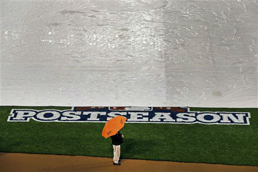 A tarp covers the field from rainfall as an usher stands guard before Game 1 of the American League division baseball series between the Baltimore Orioles and the New York Yankees on Sunday, Oct. 7, 2012, in Baltimore. &#40;AP Photo&#47;Patrick Semansky&#41; <span class=meta>(AP Photo&#47; Patrick Semansky)</span>