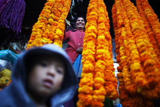 A flower vendor woman smiles as she waits for the customer during Tihar festival in Katmandu, Nepal, Monday, Nov 12, 2012. Tihar, the festival of lights is one of the most important of all Hindu festival, where they worship Goddess Laxmi, the Goddess of wealth and decorated their houses with oil lamps. The five day festival starting from the thirteenth day of the waning moon in October also meant for life and prosperity. (AP Photo/Niranjan Shrestha)