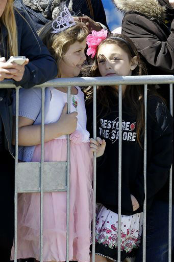A young girl, left, wears a tiara while another girl wears a sweatshirt reading &#34;Restore the Shore&#34; as they wait behind a barricade hoping to catch a glimpse of Britain&#39;s Prince Harry at the Casino Pier during a tour of the area hit by Superstorm Sandy, Tuesday, May 14, 2013, in Seaside Heights, N.J.   New Jersey sustained about &#36;37 billion worth of damage from the storm. &#40;AP Photo&#47;Julio Cortez&#41; <span class=meta>(AP Photo&#47; Julio Cortez)</span>