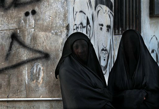Bahraini women watch the funeral of Habib Ibrahim, 88, a man whose family and opposition rights activists allege died from tear gas fired by police during earlier clashes in Malkiya village, Bahrain, Sunday, Jan 13, 2013. Graffiti on the wall reads,&#34; Down Hamad,&#34; referring to the king of Bahrain, along with images of people who died in the unrest. &#40;AP Photo&#47;Hasan Jamali&#41; <span class=meta>(AP Photo&#47; Hasan Jamali)</span>