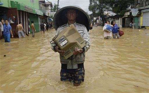 "<div class=""meta ""><span class=""caption-text "">A resident carries a monitor along a flooded road in Marikina City, east of Manila, Philippines, Wednesday Aug. 8, 2012. Widespread flooding battered a million others and paralyzed the Philippine capital began to ease Wednesday as cleanup and rescue efforts focused on a large number of distressed residents, some still marooned on their roofs. (AP Photo/Aaron Favila) (AP Photo/ Aaron Favila)</span></div>"