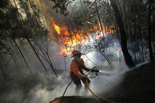 A firefighter steps back while working to douse a fire in Alvaiazere, center Portugal, Tuesday, Sept. 4, 2012. A Portuguese official says authorities have asked other European countries to send help as the country&#39;s firefighters struggle to contain forest blazes being fueled by high temperatures and strong winds. More than 1,700 firefighters, almost 500 vehicles and 13 aircraft fought blazes mostly in the north of the country. &#40;AP Photo&#47;Francisco Seco&#41; <span class=meta>(AP Photo&#47; Francisco Seco)</span>