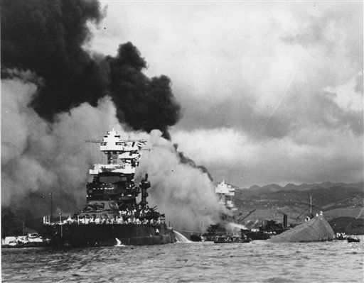 Torpedoed and bombed by the Japanese, the battleship USS West Virginia begins to sink after suffering heavy damage, center, while the USS Maryland, left, is still afloat in Pearl Harbor, Oahu, Hawaii, in a Dec. 7, 1941 file photo.   <span class=meta>(AP Photo&#47; Anonymous)</span>