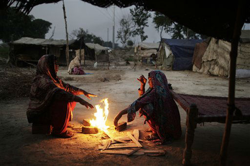 A Pakistani woman, who was displaced from her village in Pakistan&#39;s Sindh province by flooding in 2010, sits with her daughter around a fire outside their makeshift home, in a slum on the outskirts of Islamabad, Pakistan, early Monday, Oct. 8, 2012. &#40;AP Photo&#47;Muhammed Muheisen&#41; <span class=meta>(AP Photo&#47; Muhammed Muheisen)</span>