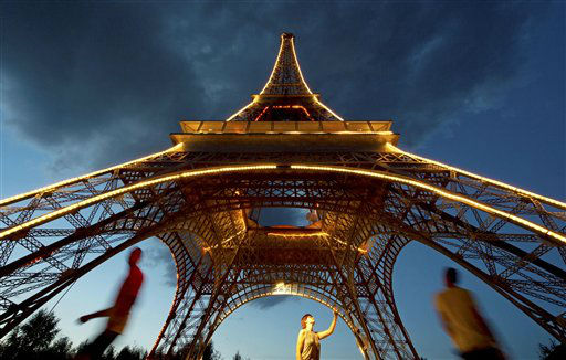 People walk beside  an illuminated model of the Eiffel Tower  &#40;12 meters high&#41; in the landscape park Miniwelt &#40;Miniworld&#41; during the sunset in Lichtenstein, eastern Germany, Wednesday, Aug. 29, 2012. The cultural park Miniworld presents about 100 original and true-to detail buildings and technical facilities at a 1:25 scale ranging on an area of 6,5 hectares. All buildings invite the visitors to take a walk through the last 3,500 years of building history, moving from the ancient world to present. &#40;AP Photo&#47;Jens Meyer&#41; <span class=meta>(AP Photo&#47; Jens Meyer)</span>