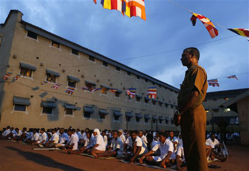 Sri Lankan prison officer stands guard as inmates pray during a religious ceremony at Welikada prison on the eve of the new year in Colombo, Sri Lanka, Monday, Dec. 31, 2012.  Inmates of the Welikada prison, one of the largest prisons in Sri Lanka housing over four thousand prisoners, invoked blessings and ushered in the new year by engaging in Buddhist rituals. &#40;AP Photo&#47;Eranga Jayawardena&#41; <span class=meta>(AP Photo&#47; Eranga Jayawardena)</span>