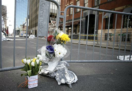 Flowers sit at a police barrier near the finish line of the Boston Marathon in Boston Tuesday, April 16, 2013. The bombs that ripped through the crowd at the Boston Marathon, killing at least three people and wounding more than 170, were fashioned out of pressure cookers and packed with shards of metal, nails and ball bearings to inflict maximum carnage, a person briefed on the investigation said Tuesday. &#40;AP Photo&#47;Winslow Townson&#41; <span class=meta>(AP Photo&#47; Winslow Townson)</span>