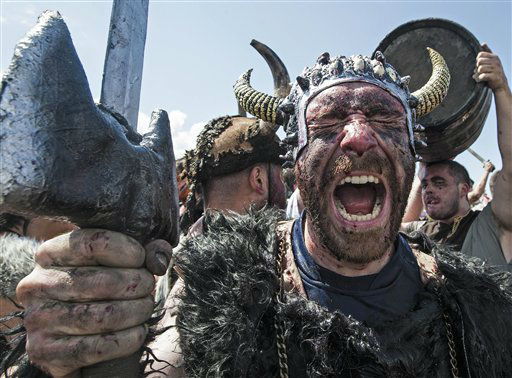 Revelers dressed as Viking warriors celebrate holding weapons, in Catoira Spain, Sunday Aug. 5, 2012 during the annual Viking Festival. The Festival, that takes place on the first Sunday of August, commemorates the Viking raids on the northwestern coasts of Spain around 1000-years ago. &#40;AP Photo&#47;Lalo R. Villar&#41; <span class=meta>(AP Photo&#47; Lalo R. Villar)</span>